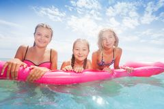 El grupo de muchachas en los matrass rosados nada en el mar Fotos de archivo libres de regalías