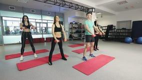 El grupo de muchachas felices entrena en el gimnasio con pesas de gimnasia almacen de video