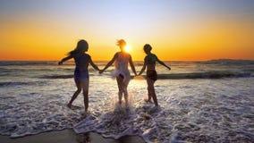 El grupo de muchachas felices salta sobre ondas del mar en la playa en la puesta del sol Imágenes de archivo libres de regalías