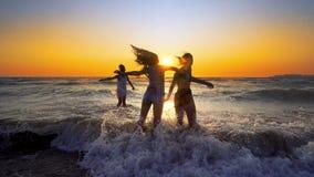 El grupo de muchachas felices salta sobre ondas del mar en la playa en puesta del sol Imagenes de archivo
