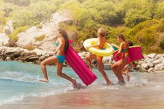 El grupo de muchachas de los niños corre en la agua de mar Fotografía de archivo