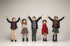 El grupo de muchachas y de muchachos hermosos en un fondo en colores pastel Foto de archivo
