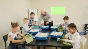 El grupo de muchachos intenta diseñar sus primeros robots y coches plásticos en la cámara lenta engeniiring de la lección metrajes