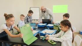 El grupo de muchachos intenta diseñar sus primeros robots y coches plásticos en la cámara lenta engeniiring de la lección almacen de video