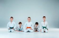 El grupo de muchachos y de muchacha que luchan en el entrenamiento del Aikido en escuela de artes marciales Forma de vida y conce Fotografía de archivo