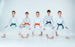 El grupo de muchachos y de muchacha que luchan en el entrenamiento del Aikido en escuela de artes marciales Forma de vida y conce Imagen de archivo