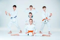 El grupo de muchachos y de muchacha que luchan en el entrenamiento del Aikido en escuela de artes marciales Forma de vida y conce Imágenes de archivo libres de regalías