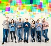 El grupo de muchachos y de muchachas conectó con sus smartphones Concepto de Internet y de red social imagen de archivo libre de regalías