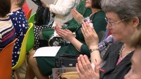 El grupo de mujer mayor de la gente está rogando en auditorio metrajes