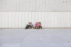 El grupo de mujeres adolescentes con tecnología aisladas en una pared con plen Fotos de archivo