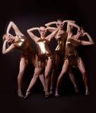 Grupo de mujeres que presentan en traje del oro Fotografía de archivo