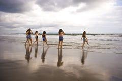El grupo de mujeres jovenes felices y emocionadas que gozan divirtiéndose en la playa hermosa de la puesta del sol en vacaciones  fotografía de archivo libre de regalías