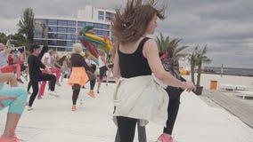 El grupo de mujeres jovenes hace exersises aerobios en la playa almacen de metraje de vídeo