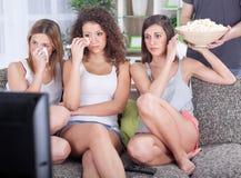 El grupo de mujeres jovenes que se sientan en el sofá que mira película triste presiona Fotografía de archivo