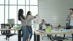 El grupo de mujeres de negocios creativas asiáticas felices alegres y los hombres gozan y teniendo baile de la diversión mientras metrajes