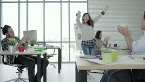 El grupo de mujeres de negocios creativas asiáticas felices alegres y los hombres gozan y teniendo baile de la diversión mientras almacen de metraje de vídeo