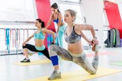 El grupo de mujeres que hacen patios del arrodillamiento estira ejercicio mientras que instructor de la aptitud que ayuda en el f Fotos de archivo libres de regalías