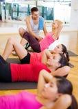 El grupo de mujeres sonrientes que el hacer se sienta sube en el gimnasio Imagenes de archivo