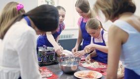 El grupo de niños aprende cocinar la comida metrajes