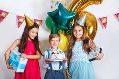 El grupo de niños celebra la fiesta de cumpleaños junto Niños que miran la torta de cumpleaños con las velas fotos de archivo