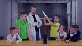 El grupo de niños explora la bobina de Tesla usando la lámpara eléctrica sobre él almacen de video