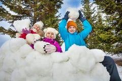 El grupo de niños felices sostiene bolas de nieve para jugar Fotos de archivo