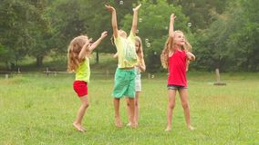 El grupo de niños juega con las burbujas de jabón en un parque Juego activo de los niños Cámara lenta metrajes