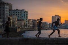 El grupo de niños juega y salta de la pared de Malecon en Atlántico en H Imagenes de archivo