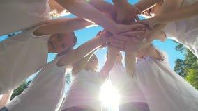 El grupo de niños realiza el saludo de motivación de los deportes con las manos en el patio del fútbol de la yarda en el día sole almacen de video