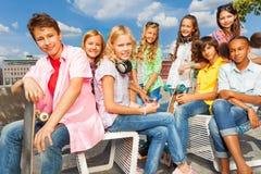 El grupo de niños se sienta en las sillas blancas con los monopatines Foto de archivo