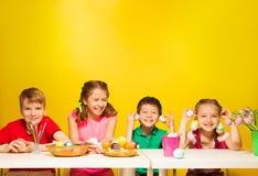 El grupo de niños se sienta en la tabla con los huevos de Pascua Fotos de archivo