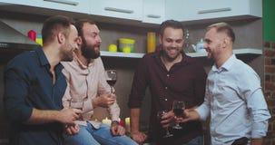 El grupo de partido étnico multi de los individuos en casa tiene un buen rato juntas, la charla y alegrías las copas de vino metrajes