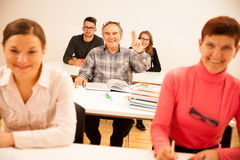 El grupo de personas de diversa edad que se sienta en sala de clase y asiste Imagen de archivo libre de regalías