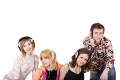 El grupo de personas en auricular escucha música. Imagen de archivo