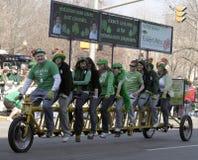 El grupo de personas en una gente larga del saludo de la bicicleta en el día del St Patrick anual desfila Imagenes de archivo