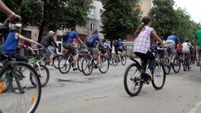 El grupo de personas enorme está montando una bicicleta metrajes