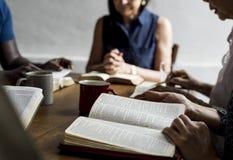 El grupo de personas está leyendo la biblia junto imágenes de archivo libres de regalías
