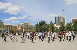 El grupo de personas grande está repitiendo danza común encendido imagen de archivo