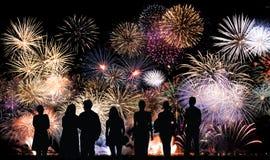 El grupo de personas mira los fuegos artificiales coloridos hermosos del día de fiesta Imagen de archivo