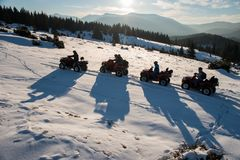 El grupo de personas que disfruta de puesta del sol, en los coches de cuatro ruedas campo a través ATV bikes en nieve en el monta Foto de archivo libre de regalías