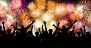 El grupo de personas que goza de los fuegos artificiales espectaculares muestra en un carnaval o un día de fiesta Fotos de archivo libres de regalías