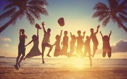 El grupo de personas que salta en la playa Imágenes de archivo libres de regalías