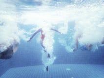 El grupo de personas saltó abajo al tiro subacuático de la piscina Imagenes de archivo