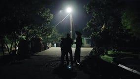 El grupo de personas se está colocando en el camino tarde en la noche y hablar Hombre africano en sombrero de un pueblo africano almacen de video