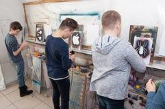 El grupo de pintura de los adolescentes de los niños con un aerógrafo coloreó brillantemente imágenes en un estudio artístico - R Foto de archivo