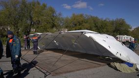 El grupo de salvadores que ponen una tienda de campo del ejército, despliega el camping en día ventoso almacen de video