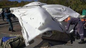 El grupo de salvadores que ponen una tienda de campo del ejército, despliega el camping en día ventoso metrajes