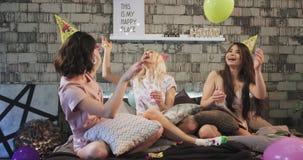 El grupo de señoras jovenes de los amigos tiene una fiesta de cumpleaños de los pijamas en un dormitorio moderno ellos que juegan metrajes