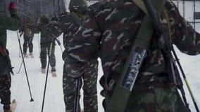 El grupo de soldados corre en los esquís en el bosque con las armas clip Soldados con el funcionamiento de los rifles de AK-47 y  metrajes