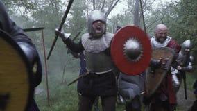 El grupo de soldados medievales acomete en la batalla con battlecry almacen de metraje de vídeo